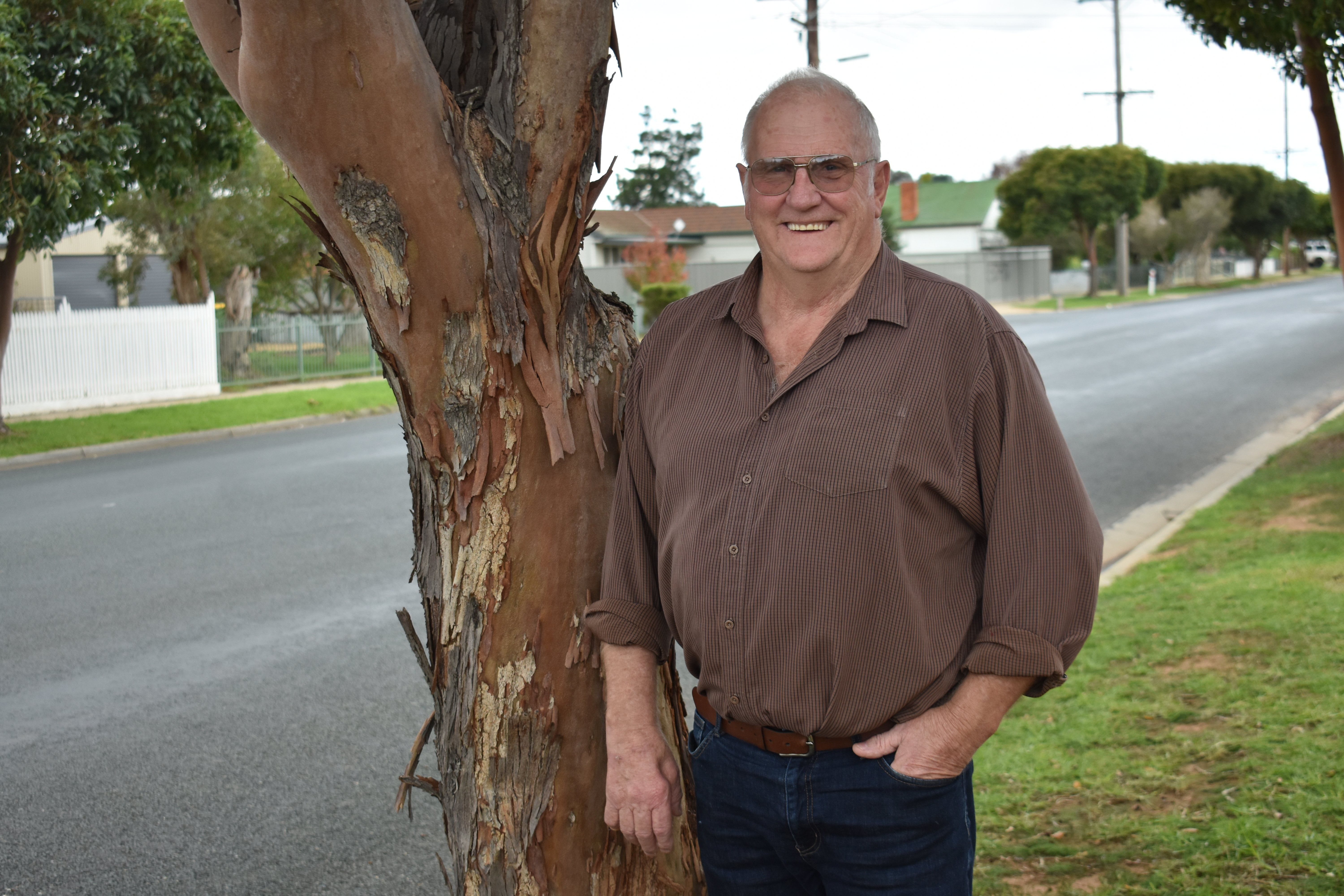 Mick Simpson standing next to a tree in suburban street