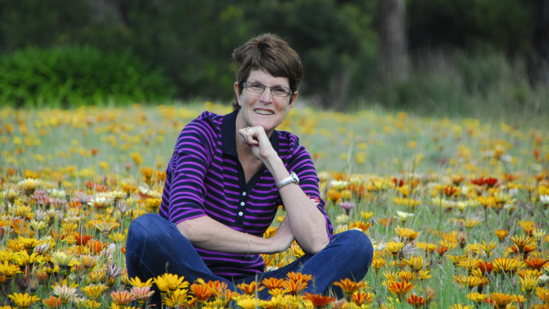 Glenda sitting cross-legged in a field of bright yellow and orange flowers