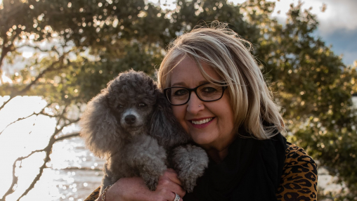 Smiling Woman Wearing Glasses and Holding a Small Grey Poodle